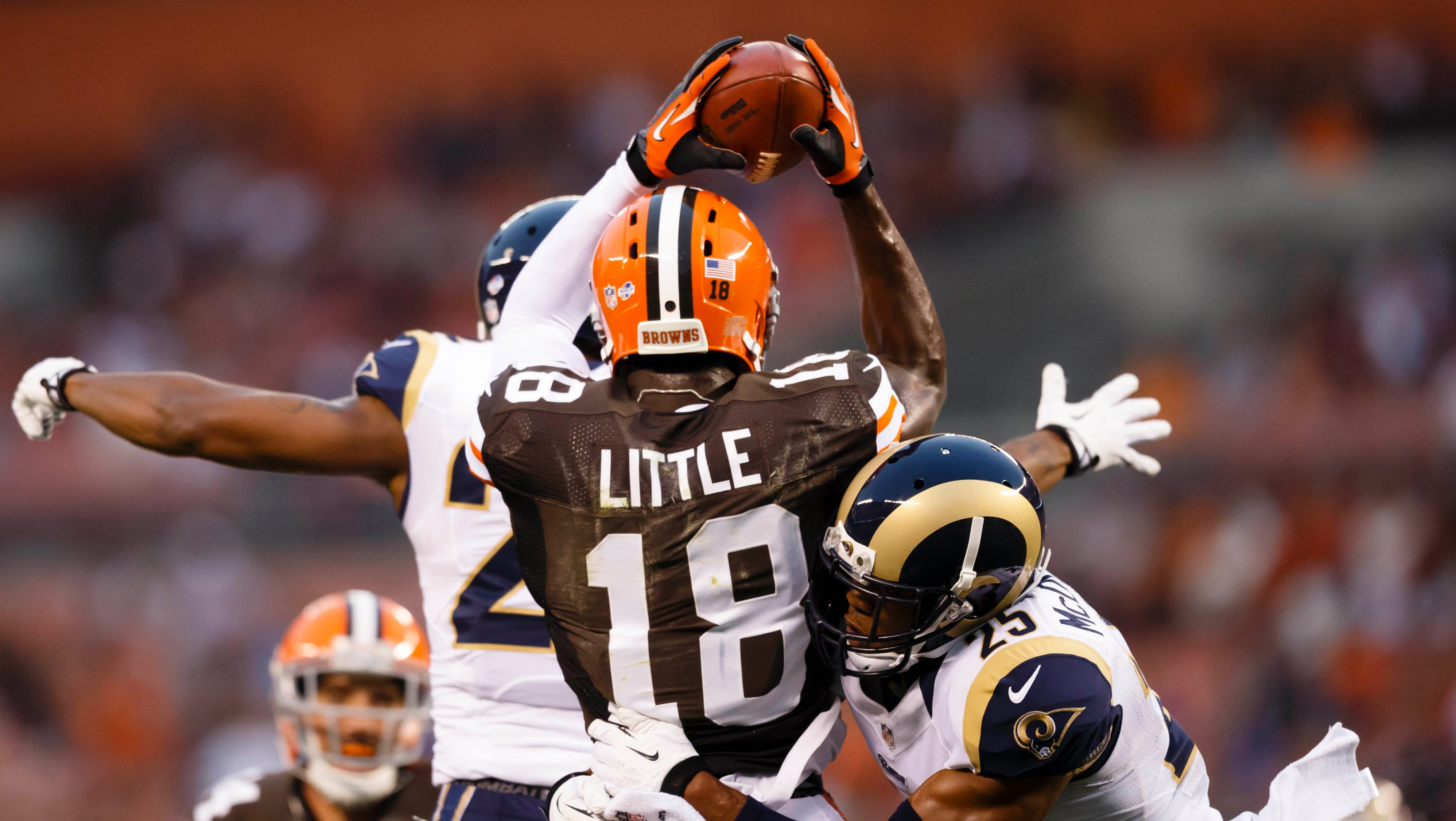 Cleveland Browns wide receiver Greg Little (18) makes a catch while St. Louis Rams free safety T.J. McDonald (25) goes in for the tackle in the first quarter at FirstEnergy Stadium.