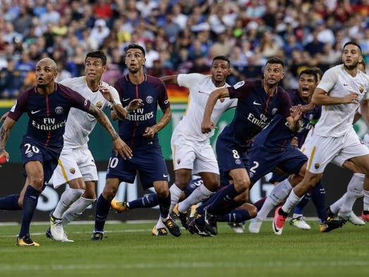 Players react to a free kick into Paris Saint-Germain