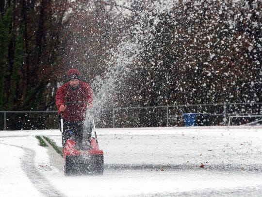 Highland Park football coaches and school employees work on removing snow from the football field for tonight's pre Thanksgiving Day football against Metuchen. On Wednesday November 26,2014 Photo: Mark R. Sullivan/Staff Photographer