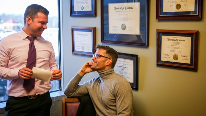 Ryan Messer (left) and Jimmy Musuraca-Messer look at an ultrasound photo of their son, Olivier, on February 5 at the Institute for Reproductive Health.