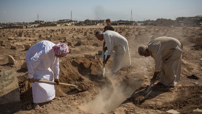 In this Oct. 2, 2017 photo, family members bury their relative in a graveyard in Mosul after his body was exhumed hours earlier.