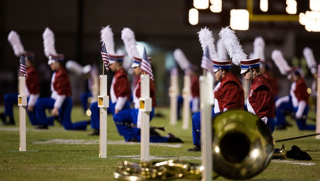 The Mountain View marching band kneels Oct. 30 by crosses that they put up to honor veterans during a performance.
