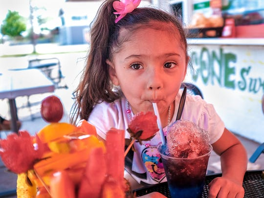 Gyzell Hunt knows how to beat the heat with a raspa or shaved flavored ice served up at Mexicone in Lansing Sunday, May 27, 2018.