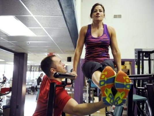 Shelby Dietz suspends herself on parallel bars with the help of her personal trainer, Evan Branin. Proponents of strength and body weight training say building muscle helps people get and stay fit because people who have more muscle burn more calories long after the workout has ended. Photo by Daily Record/Sunday News -- Chris Dunn.