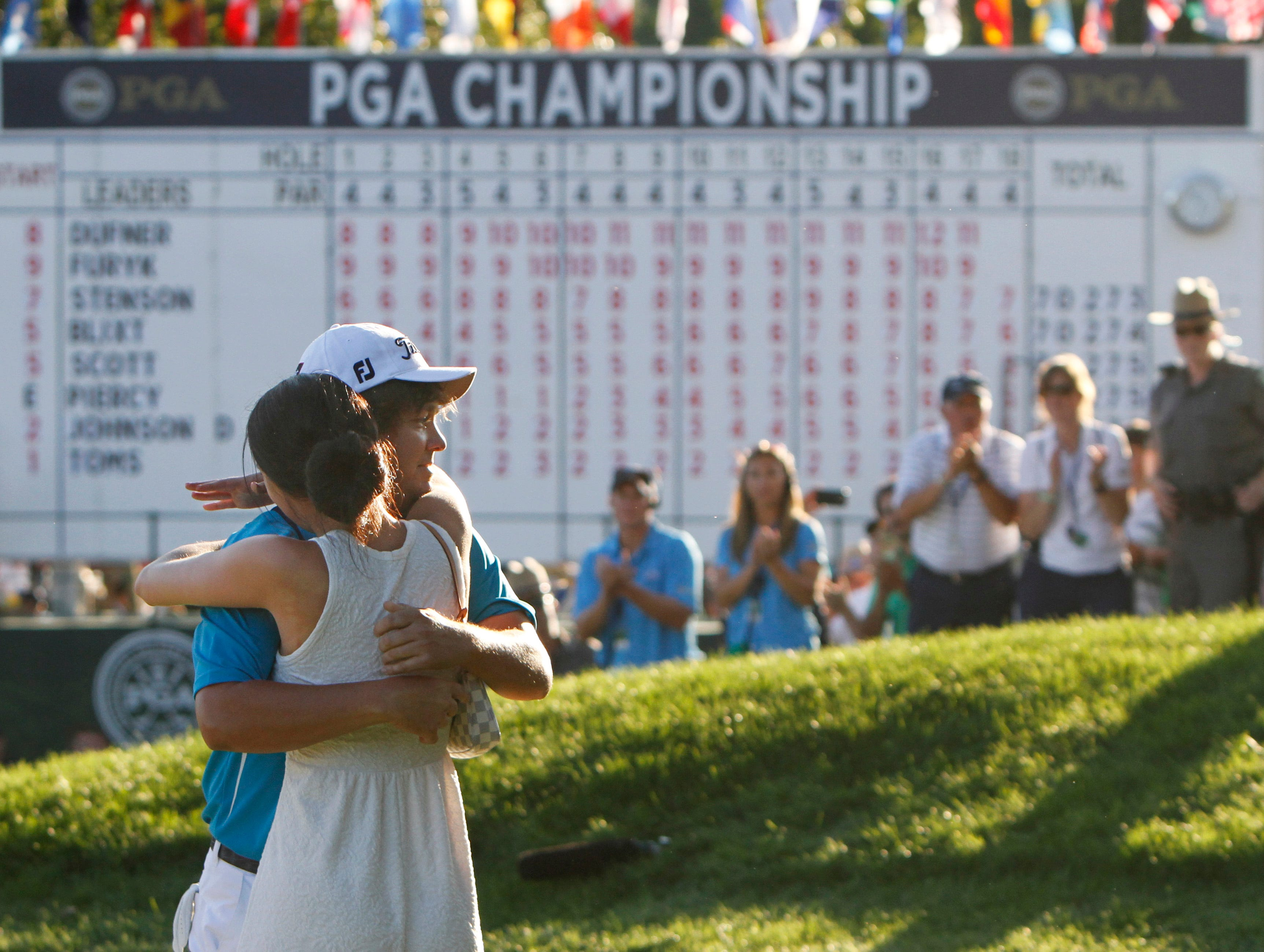 Jason Dufner hugs wife on the 18th green following his two stroke victory at the final round of the 95th PGA Championship Sunday, Aug. 11, 2013 at Oak Hill Country Club in Pittsford.