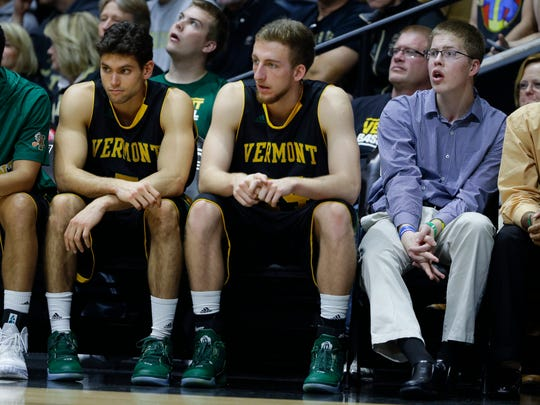 Josh Speidel, right, sits on the bench with Vermont players Dylan Sinnickson, left, and Nate Rohrer in the first half of an NCAA college basketball game against Purdue in West Lafayette, Ind., Sunday, Nov. 15, 2015. Speidel is recovering from a Feb. 1 auto accident that resulted in a traumatic brain injury.  (AP Photo/Michael Conroy)