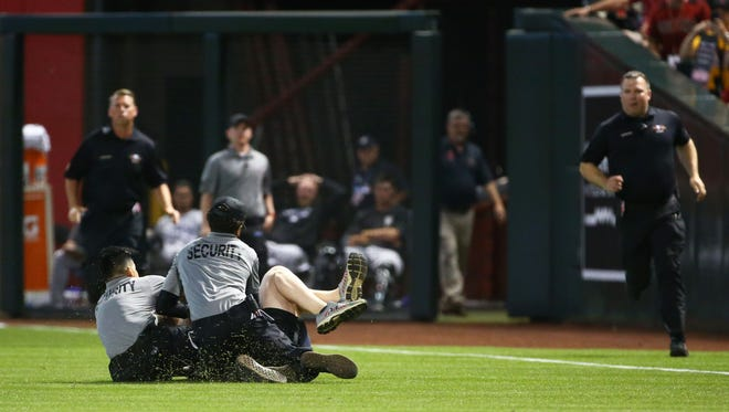 A man running across the diamond is tackled by security in right field causing a delay in the Arizona Diamondbacks game in the 3rd inning on Mar. 29, 2018 during the season opener at Chase Field in Phoenix, Ariz.