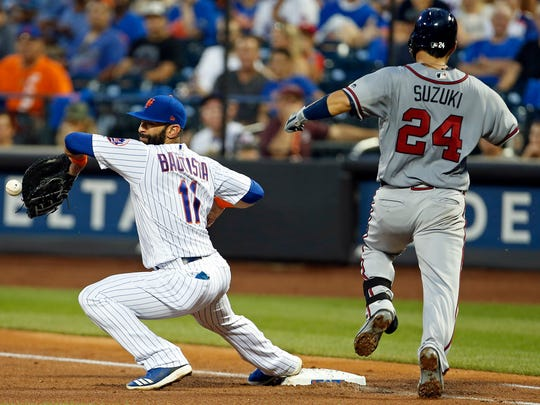 Atlanta Braves catcher Kurt Suzuki (24) is safe at first base as New York Mets first baseman Jose Bautista (11) can't handle the throw during the fourth inning at Citi Field.