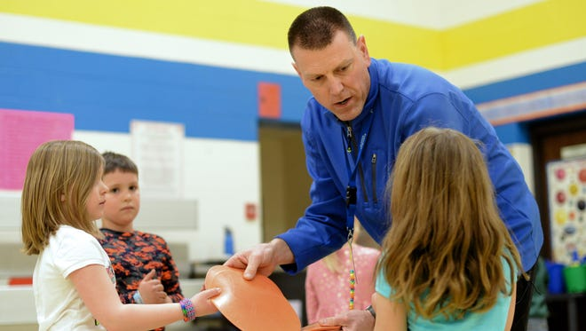Golden Apple recipient Chris Wendorf talks with his students as they help clean up after an activity focusing on rolling, throwing and catching skills at Sunnyside Elementary in Pulaski.