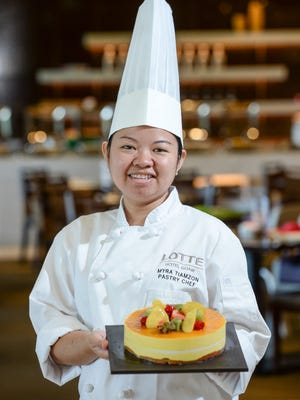 Pastry Chef Myra Tiamzon displays a mango tropical cake at the Lotte Hotel Guam lobby in Tumon on Monday, Dec. 21.