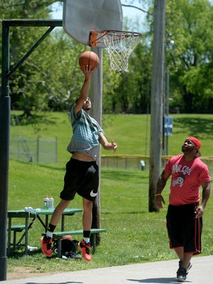 Trey Buchannon and DeMarco Clinton play basketball Thursday, May 19, 2016, at Clear Creek Park in Richmond.