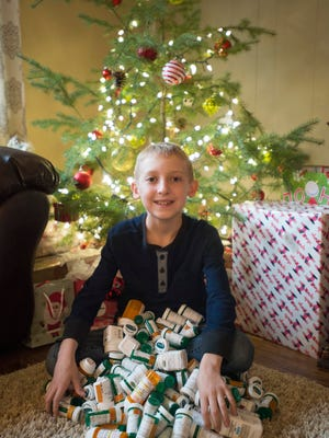 Parker Hobbs shows off the pile of pill bottles acquired during years of cancer treatments at his home in Wellington Thursday, Dec. 22, 2016. The 10-year-old had his last treatment for leukemia this week.