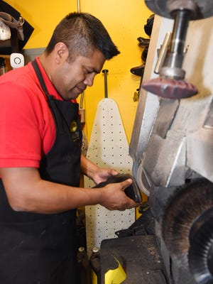 Refugio Contreras, president and owner of C&F Shoe Repair in the City of Poughkeepsie, works on fixing a shoe.