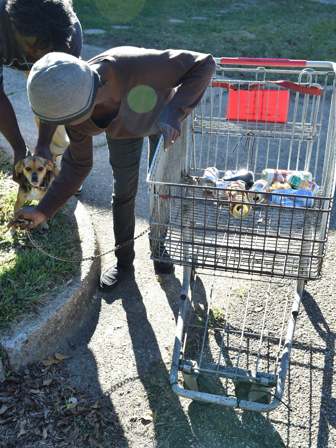 Patricia Aaron prepares her dog Chip for their journey to collect cans around Arron's neighborhood.