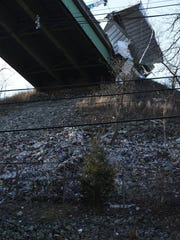 A tractor trailer hangs off the side of an overpass