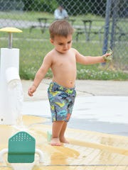 Two-year-old Benjamin Gierak enjoys the interactive water feature at Botsford pool in Livonia.