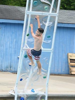 "Hunter Brown is thrilled to climb the new ""Aquaclimb"" wall at Botsford Pool in Livonia."