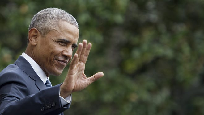 President Obama waves as he walks across the White House lawn.