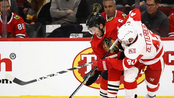 Nick Schmaltz of the Blackhawks and Henrik Zetterberg of the Red Wings battle for the puck along the boards on Sunday in Chicago.