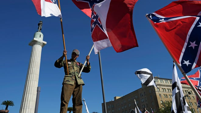 A protester advocating for the preservation of Confederate monuments in New Orleans holds Confederate battle flags earlier this month in New Orleans.