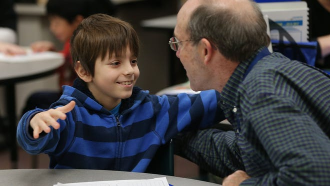 Fourth-grader William Stein gives mentor Jon Swanson a hug after stopping by to see him during a mentoring session at Stout Field Elementary. William worked on his reading with Swanson last year. The Wayne Township Schools program, called HOSTS, stands for Help One Student to Succeed.