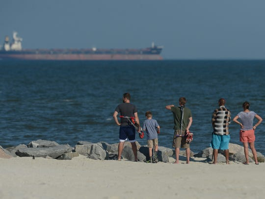 A small group of people watches a recovery effort at