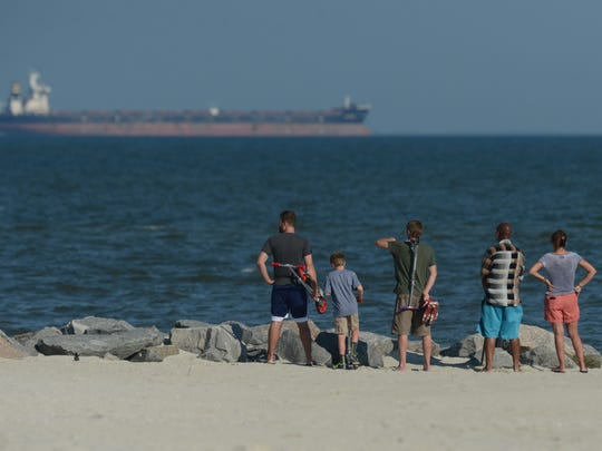 A small group of people watches a recovery effort at Cape Charles Beach on Monday, June 22, 2015. The Coast Guard was alerted to a report of a missing swimmer Sunday night. According to the Coast Guard a 15-year-old swimmer went missing near the town's fishing pier.