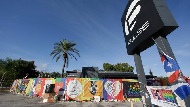 Artwork and signatures cover a fence around the Pulse nightclub, scene of a mass shooting, on Nov. 30, 2016, in Orlando.
