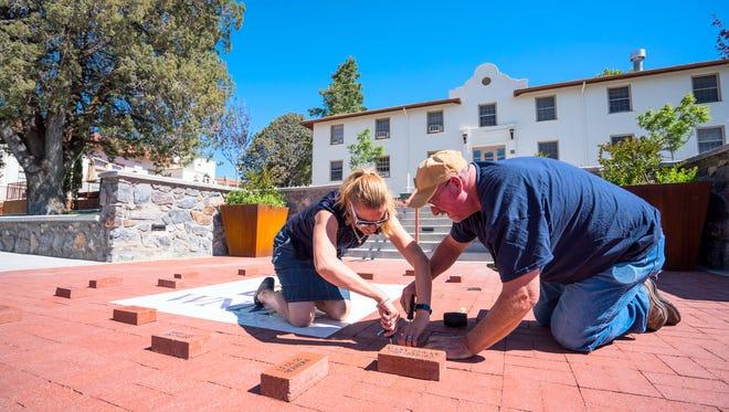 University Foundation Executive Director Jodi Edens-Crocker helps WNMU maintenance official Bill Burns make room for a Legacy Brick.