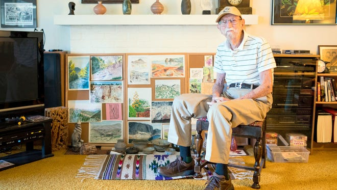 Eugene Lewis sits among artwork collected by his late wife Eulalia, whom he is honoring with a new named WNMU art scholarship.