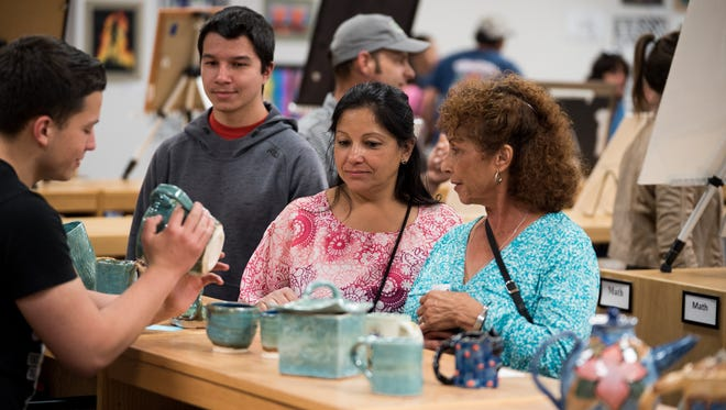 A student points out the details of pottery he made in a Western New Mexico University Expressive Arts studio class.