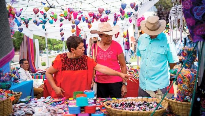 A Latin American artisan shows Fiesta Latina! attendees her wares.