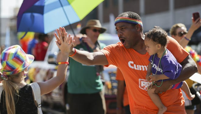 A man high-fives a young girl as he and his daughter  walk in the  Circle City IN Pride Parade on June 11, 2016, in Downtown Indianapolis.