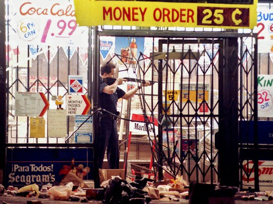 A Los Angeles police officer takes aim at a looter in a market April 30, 1992, the second night of rioting in the city.