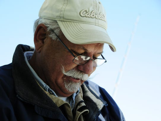 Capt. Ron Cutler checks a fishing lure aboard the Model