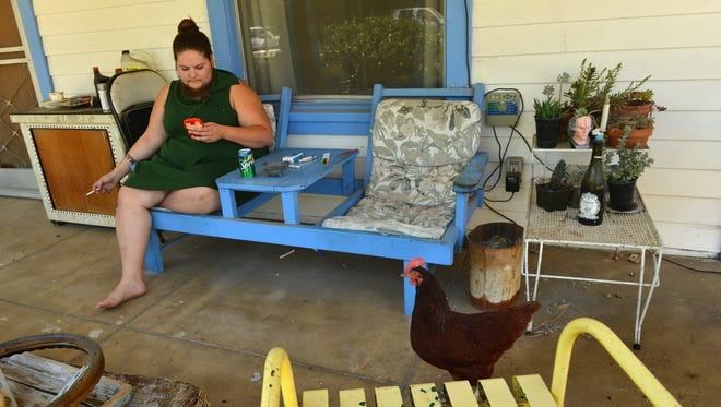 A pet chicken struts by Dakota Cooke as she sits on the porch of her family home in Fillmore.