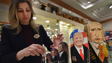 An employee displays traditional Russian wooden nesting dolls, Matryoshka dolls, depicting US President-elect Donald Trump, Russian President Vladimir Putin and other political leaders at a gift shop in central Moscow on Jan. 16, 2017,.