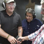 U.S. Army veteran David Gorlewski, foreground, who served seven-and-a-half tours in Iraq and Afghanistan, consults with Pete Emhoff, behind Gorlewski at left, and Mark Freier at Peacemakers Indoor Gun Range in Howell.
