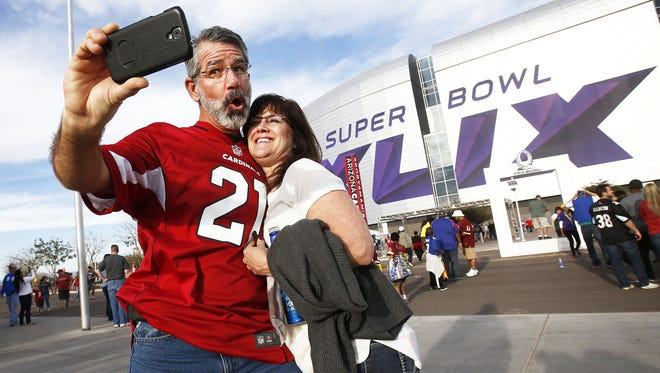 David and Anne Biermann from Sedona, AZ, take a selfie of the Super Bowl XLIX sign on their way to watch the Pro Bowl on Sunday, Jan. 25, 2015 in Glendale, AZ.