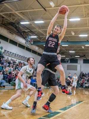 Marshall's Jeremy Luciani (22) gets a rebound during first half action of district finals against Pennfield Friday evening.