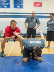 Kellogg Community College Police Academy Instructor Rob Miller demonstrates proper technique to his class in Miller Gymnasium.