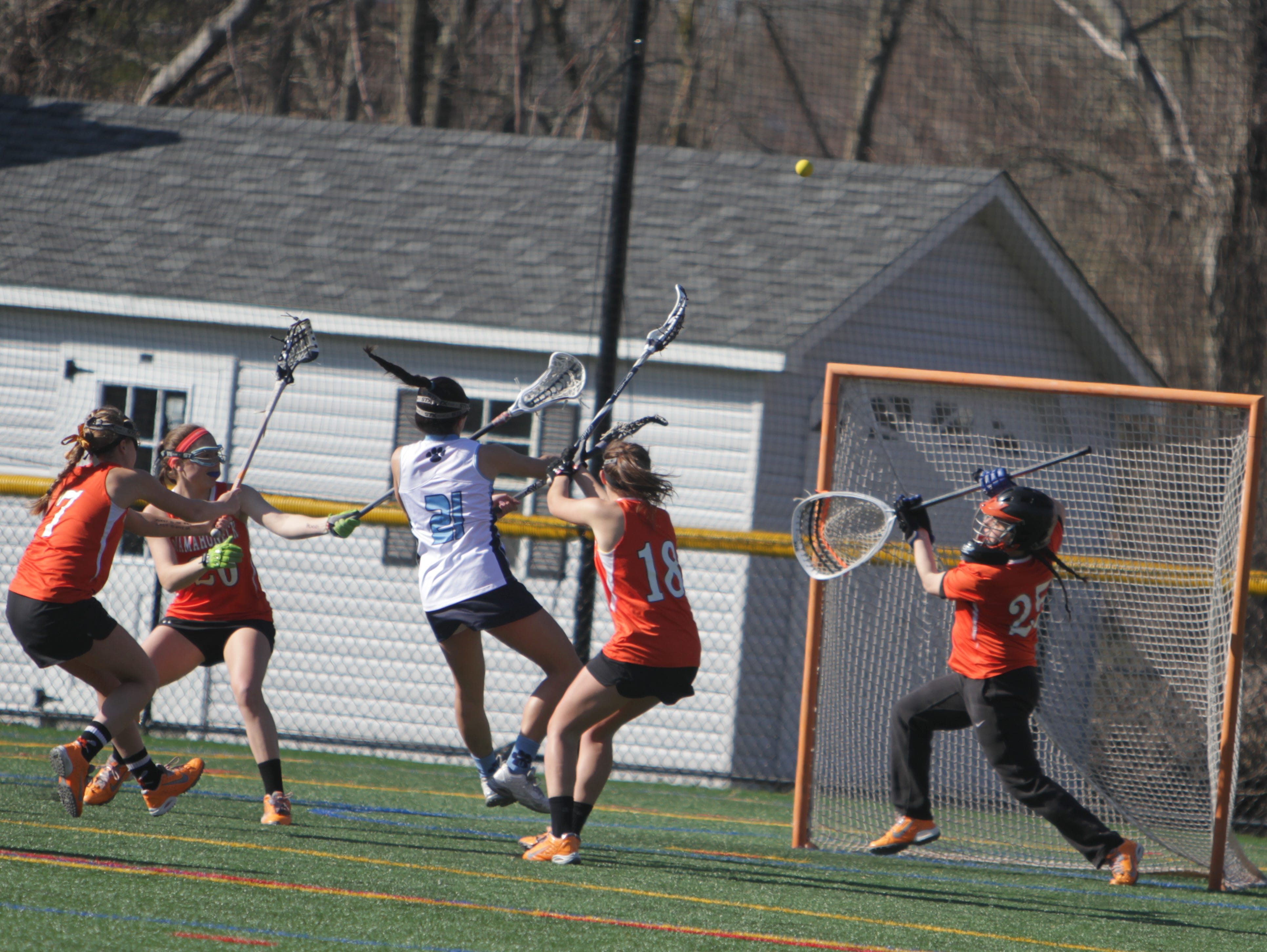Ursuline's Julianna Sullivan (white) rips a shot attempt over Mamaroneck goalie Talia Land during a Section 1 girls lacrosse game between Ursuline and Mamaroneck at the Ursuline School on Thursday, April 14th, 2016. Mamaroneck won 12-10.