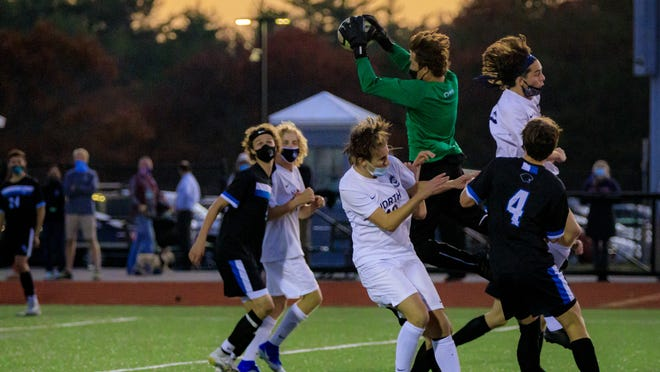 Plymouth South goaltender Enzo Gill , center, leaps to catch the ball in the middle of a big crowd.