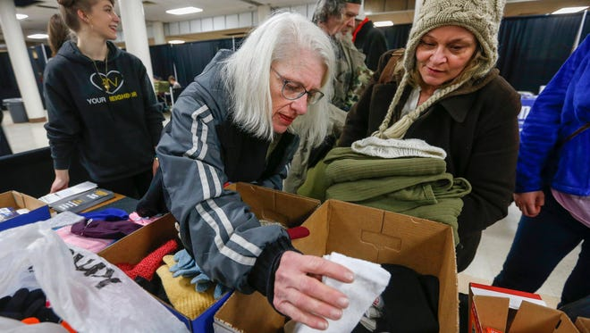 Bennie Sams, left, and Janie Wilson pick out socks and other items from a table set up by The Venues church during the homeless count at the Shrine Mosque last Thursday. More than 350 individuals were counted.