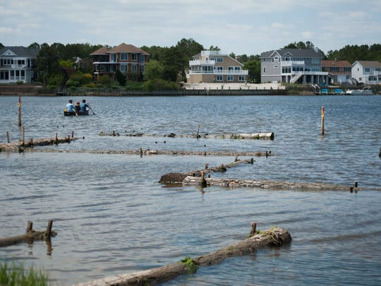 People paddle past a living shoreline that was recently created in Bethany Beach.
