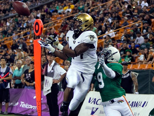 Army Black Knights defensive back Steven Johnson pulls in an interception over Hawaii Warriors wide receiver Chris Gant during the first quarter at Aloha Stadium.
