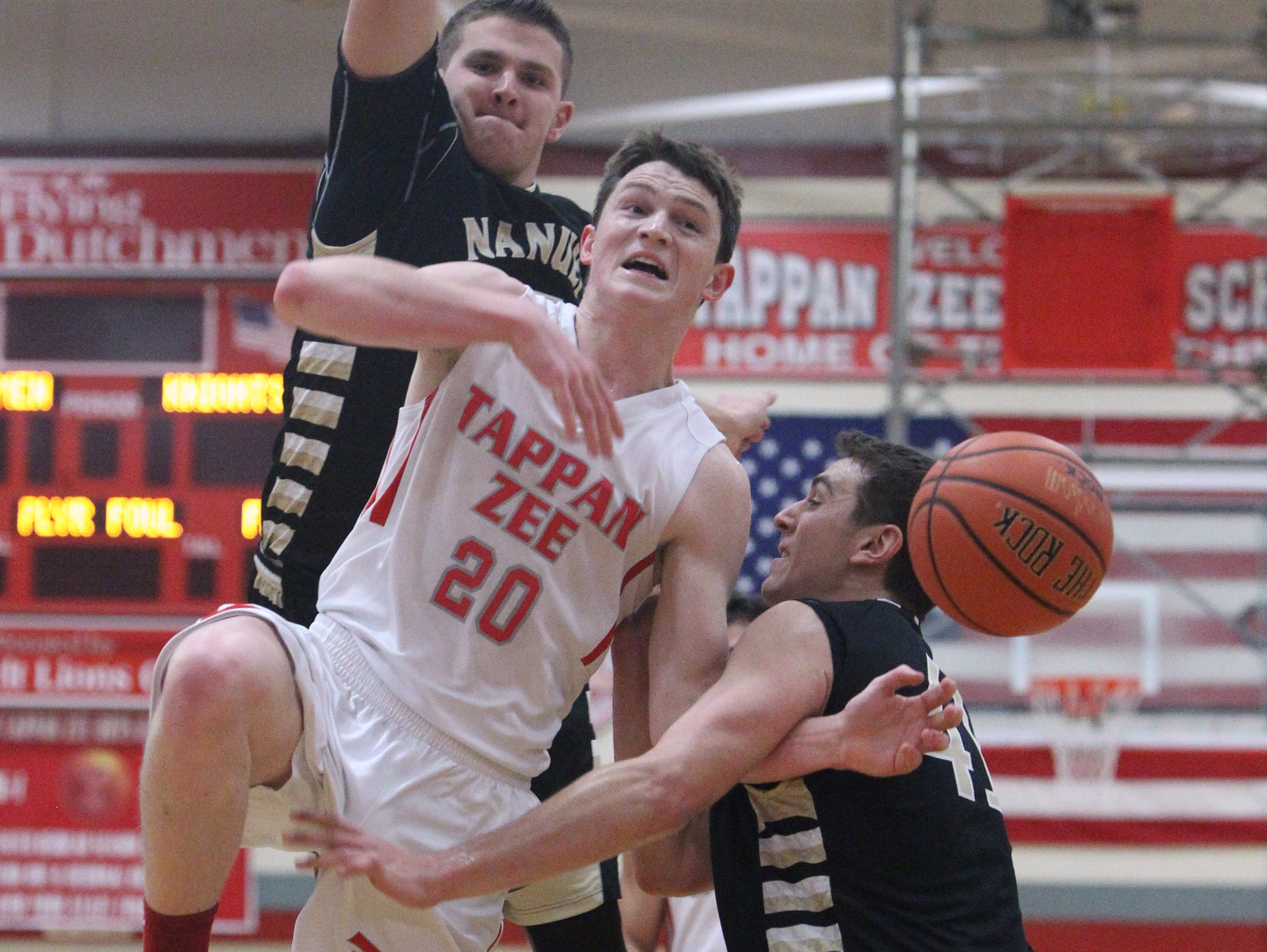 Tappan Zee's Kevin Lynch is fouled while driving on Nanuet's Jordan Landsman, left, and Aedan Lombardo (41) during their game at Tappan Zee Jan. 6, 2016. Tappan Zee won 59-46.