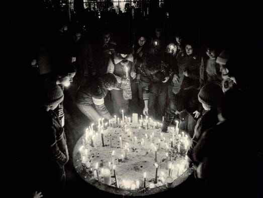 Rochesterians honor the late John Lennon by placing candles in a large flower pot at the end of a vigil held in memory of the slain musician at Manhattan Square Park on Dec. 9, 1980.
