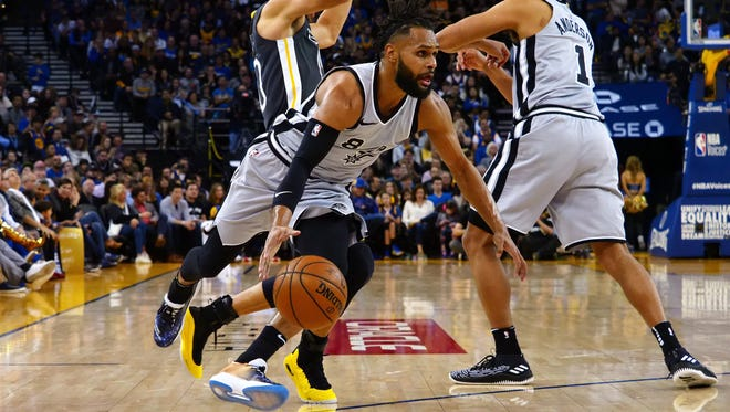 San Antonio Spurs guard Patty Mills (8) drives in around Golden State Warriors guard Stephen Curry (30) with San Antonio Spurs forward Kyle Anderson (1) during the third quarter at Oracle Arena.