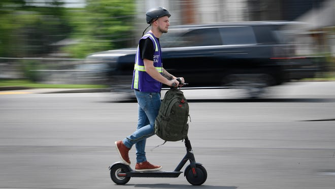 A rider speeds along 12th Ave. South atop a Bird scooter Tuesday, May 15, 2018, in Nashville, Tenn.